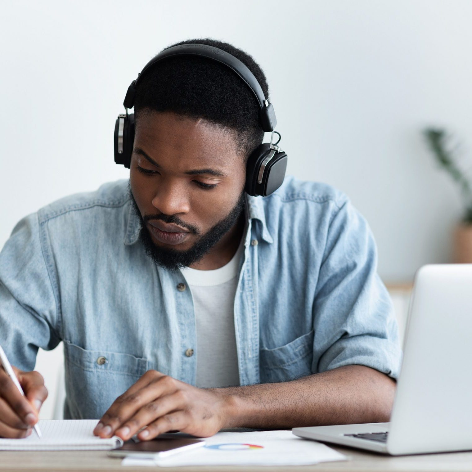Concentrated african american guy in headphones studying foreign language online through video conference and making notes in notebook, panorama with copy space